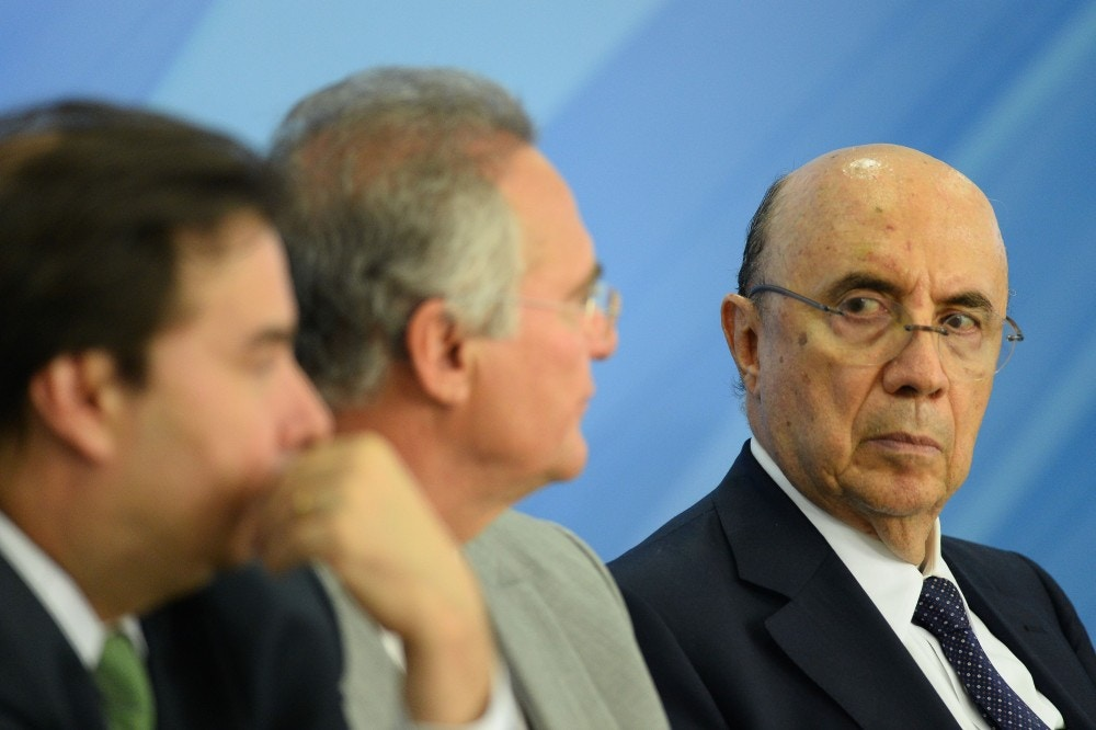 The president of Brazil's Chamber of Deputies Rodrigo Maia (L), the president of the Senate Renan Calheiros (C), and Finance Minister Henrique Meirelles (R) gesture during the announcement of new measures to stimulate the economy in the Planalto Palace on December 15, 2016 in Brasilia. / AFP / ANDRESSA ANHOLETE (Photo credit should read ANDRESSA ANHOLETE/AFP/Getty Images)