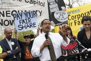 Rep. Keith Ellison, D-Minn. joins low-wage workers at a rally outside the Capitol in Washington, Monday, April 28, 2014, to urge Congress to raise the minimum wage as lawmakers return to Washington following a two week hiatus. Democratas vêm pressionando pelo aumento do salário mínimo, mas mesmo se a lei for aprovada no Senado, é certo que será ignorada pelo Congresso, controlado por republicanos.  (AP Photo)