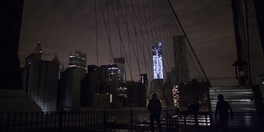 FILE- In this Nov. 1, 2012 file photo, much of lower Manhattan remains dark, as viewed from the darkened Manhattan side of the pedestrian walkway of the Brooklyn Bridge in New York. Americans are paying more to maintain the nation's electrical grid than a decade ago, but they appear to be getting little for their money from utility services that are no more reliable and in some cases seem to be getting worse. An Associated Press analysis of utility spending and reliability nationwide found that electric customers are spending 43 percent more than they did in 2002 to build and maintain local electric infrastructure. Since then, power outages have remained infrequent; but when the lights do go out, it now takes longer to get them back on. (AP Photo/Craig Ruttle, File)