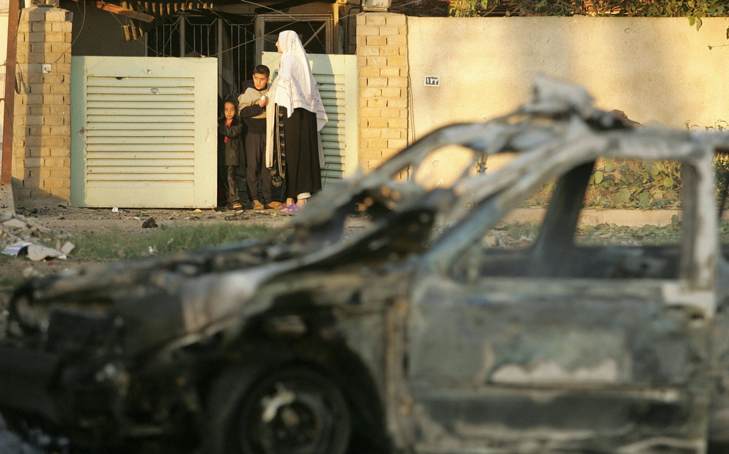BAGHDAD, IRAQ:  An Iraqi family looks out of the front gate of their home following a car bomb 19 November 2004, in Baghdad. Three people were killed, a policeman and two civilians, and 10 others wounded when a suicide car bomb exploded in Baghdad, police said. AFP PHOTO/MARWAN NAAMANI  (Photo credit should read MARWAN NAAMANI/AFP/Getty Images)