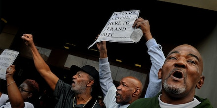 BALTIMORE, MD-MAR 10: (left with fist in the air, wearing hat) Gerald Dent, who served 41 years in prison joined (center, with sign) James Featherstone (he served 35 years in prison) and (R) Niles Ringgold (Ringgold served 40 years in prison) at the rally for felon voting rights. They chanted,