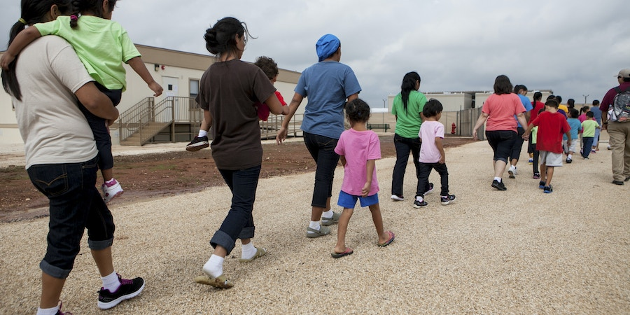 DILLEY, TEXAS - May 14, 2015: Residents walk through the facility grounds to eat lunch at the cafeteria. The South Texas Family Residential Center in Dilley, Texas was built in December 2014 to host up to 2,400 undocumented women and children who are seeking asylum. The Dilley facility is the largest of its kind, and while residents may move freely from building to building, they are not permitted to leave the grounds.