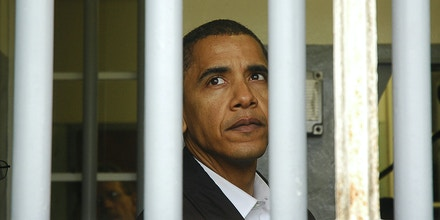 Barak Obama, US senator for Illinois, looks out of the window of Mandela's jail cell, 20 August 2006, on Robben Island, about six kilometres from the city, in Table Bay. Obama was visiting the island prison museum, where Nelson Mandela was imprisoned for about 18 years, as part of a larger visit to the country. AFP PHOTO/RODGER BOSCH / AFP / RODGER BOSCH        (Photo credit should read RODGER BOSCH/AFP/Getty Images)