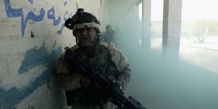 NAJAF, IRAQ - AUGUST 16: American soldiers from the 1st Cavalry Division 2nd Battalion 7th Cavalry run through a smoke screen as they try to avoid sniper fire during an offensive operation August 16, 2004 in Najaf, Iraq. Fighting continued in the holy city of Najaf after peace talks broke down between the Iraqi government and rebel Shiite Muslim militia. (Photo by Joe Raedle/Getty Images)