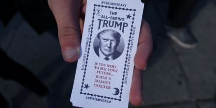 A man hold a card dispensed from the 'All-Seeing Trump', a fortune-telling fairground attraction bearing the likeness of Republican presidential candidate Donald Trump, in New York on October 12, 2016. There's little love for Donald Trump in his hometown these days, so New York has been both tickled and repelled by a fortune-telling, Trump-in-a-box mocking his offense-dishing campaign for president. The Trump-in-a-box has been made to resemble the Zoltar machine made famous in the 1988 Hollywood movie