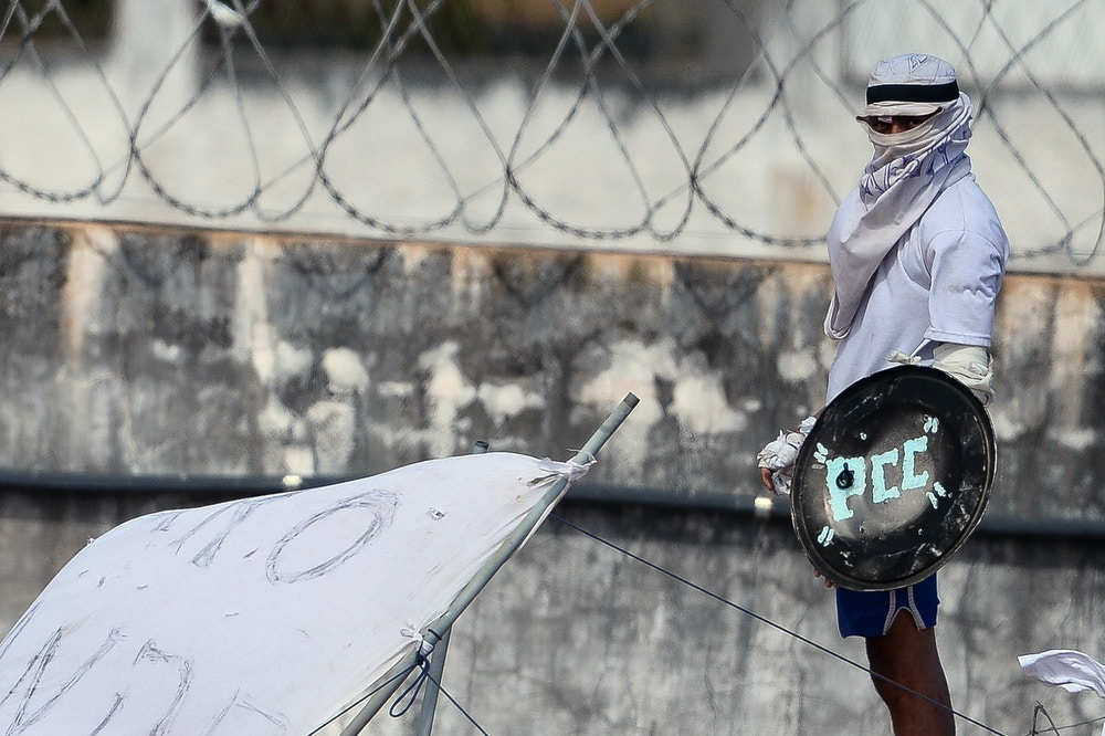 An inmate with his face covered stands on the prison roof during a rebellion in Alcacuz Penitentiary Center near Natal, Rio Grande do Norte state, northeastern Brazil on January 16, 2017.The latest in a string of brutal prison massacres involving suspected gang members in Brazil has killed 26 inmates, most of whom were beheaded. The bloodbath erupted Saturday night in the overcrowded Alcacuz prison in the northeastern state of Rio Grande do Norte. Similar violence at other jails in Brazil left around 100 inmates dead in early January. / AFP / ANDRESSA ANHOLETE (Photo credit should read ANDRESSA ANHOLETE/AFP/Getty Images)
