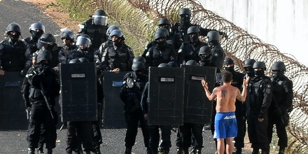 Riot police agents group and approach to negociate with an inmate's delegate (R) during a rebellion at the Alcacuz Penitentiary Center near Natal, Rio Grande do Norte state, northeastern Brazil on January 16, 2017.The latest in a string of brutal prison massacres involving suspected gang members in Brazil has killed 26 inmates, most of whom were beheaded. The bloodbath erupted Saturday night in the overcrowded Alcacuz prison in the northeastern state of Rio Grande do Norte. Similar violence at other jails in Brazil left around 100 inmates dead in early January. / AFP / ANDRESSA ANHOLETE (Photo credit should read ANDRESSA ANHOLETE/AFP/Getty Images)
