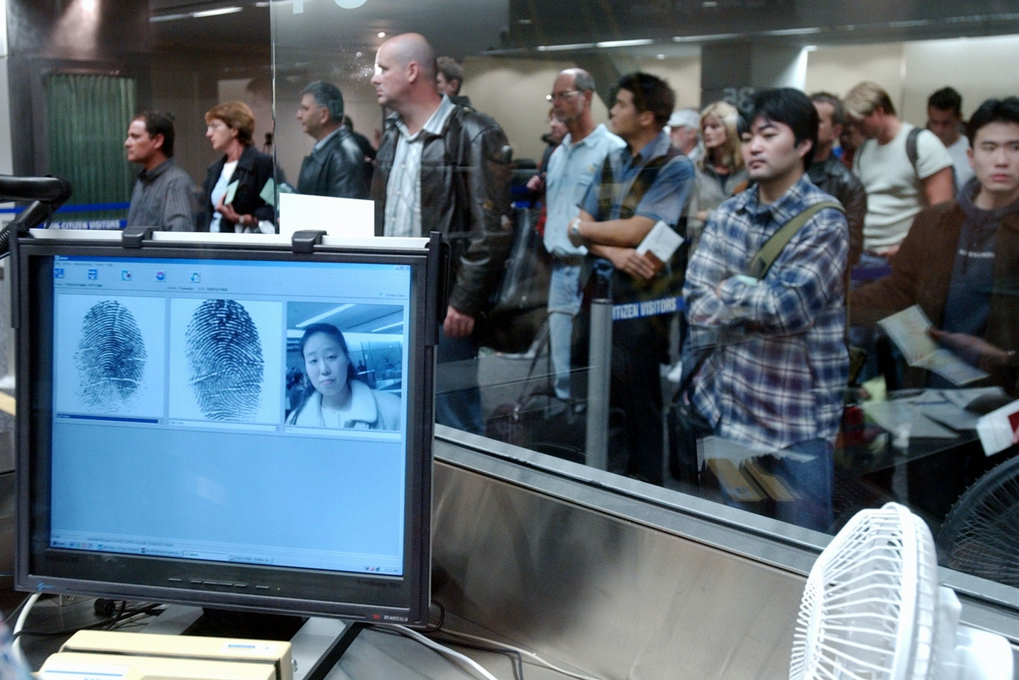 Visitors wait in line to be fingerprinted and photographed at the U.S. Customs check point at San Francisco International Airport in San Francisco Monday, Jan. 5, 2004. Officials began using the US-VISIT system on Monday to scan fingerprints and take photographs of arriving foreigners as part of a program aimed at preventing and trapping possible terrorists. (AP Photo/Marcio Jose Sanchez)