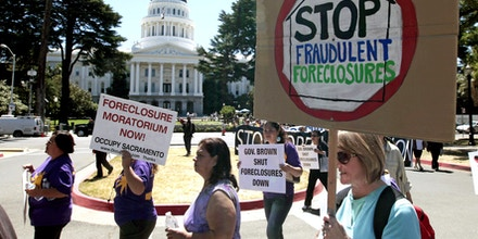Demonstrators march past the state Capitol during a protest on home foreclosures in Sacramento, Calif.,  Monday, June 25, 2012.  About 100 protestors gathered at the state Capitol and marched to two different banks, demanding that the governor, attorney general and lawmakers declare an immediate moratorium on home foreclosures in the state. (AP Photo/Rich Pedroncelli)