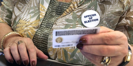 Officer of election Phyllis Booth checks a voter's ID at the Berkley voting precinct at the Ashland Fire Station #1, in Ashland, Va., Tuesday, Nov. 4, 2014. (AP Photo/Richmond Times-Dispatch, P. Kevin Morley)