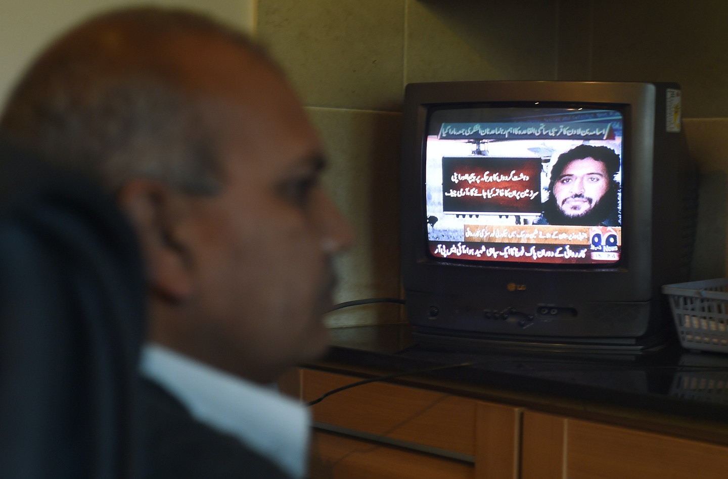 A Pakistani man watches a television broadcasting news of top Al-Qaeda leader Adnan El Shukrijumah, in Islamabad on December 6, 2014.  Pakistan's military said it had killed Shukrijumah, a senior Al-Qaeda leader wanted by the US over a 2009 plot to attack the New York subway system. Shukrijumah, one of the FBI's most wanted terrorists, was hiding in a compound in Shinwarsak, northwestern Pakistan, after fleeing from neighbouring North Waziristan tribal district where the army launched a major operation against militant bases in June, the military said.  AFP PHOTO/Farooq NAEEM        (Photo credit should read FAROOQ NAEEM/AFP/Getty Images)