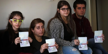 Fuad Sharif Suleman and his family show their US immigrant visas in Arbil, the capital of the Kurdish autonomous region in northern Iraq, on January 30, 2017 after returning to Iraq from Egypt, where they were prevented from boarding a plane to the US following US President Donald Trump's decision to temporarily bar travellers from seven countries, including Iraq.  / AFP / SAFIN HAMED        (Photo credit should read SAFIN HAMED/AFP/Getty Images)