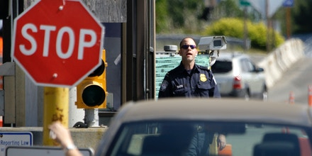A U.S. Customs and Border Protection officer looks toward a car coming toward him Saturday, May 30, 2009, at the border crossing between the U.S. and Canada, in Blaine, Wash. New rules requiring passports or new high-tech documents to cross the United States' northern and southern borders are taking effect Monday, June 1, as some rue the tightening of security and others hail it as long overdue. In 2001 a driver's license and an oral declaration of citizenship were enough to cross the Canadian and Mexican borders; Monday's changes are the last step in a gradual ratcheting up of the rules.
