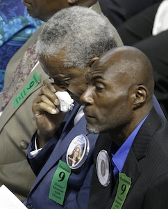 Rev. Anthony Thompson, background, husband of victim Myra Thompson, wipes his face during a memorial in Charleston, S.C., Friday, June 17, 2016 on the anniversary of the killing of nine black parishioners during bible study at Mother Emanuel AME Church. (AP Photo/Chuck Burton)