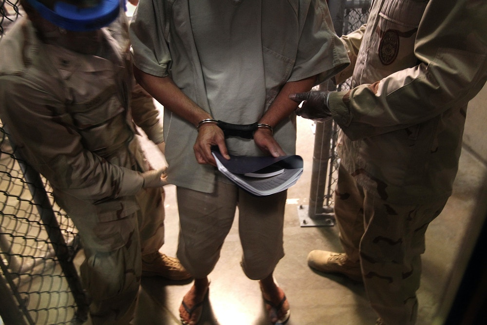 """GUANTANAMO BAY, CUBA - MARCH 30:  (EDITORS NOTE: Image has been reviewed by the U.S. Military prior to transmission.) U.S. Navy guards escort a detainee after a """"life skills"""" class held for prisoners at Camp 6 in the Guantanamo Bay detention center on March 30, 2010 in Guantanamo Bay, Cuba. U.S. President Barack Obama pledged to close the prison by early 2010 but has struggled to transfer, try or release the remaining detainees from the facility, located on the U.S. Naval Base at Guantanamo Bay, Cuba.  (Photo by John Moore/Getty Images)"""
