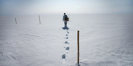 Hannah James, a Polar Field Services science technician, hikes to collect a snow sample at Summit Station, a remote outpost in Greenland, July 15, 2015. Summit Station is one of several Greenland sites where researchers gather data that will improve climate models and help predict climate change affecting future generations. (Josh Haner/The New York Times)