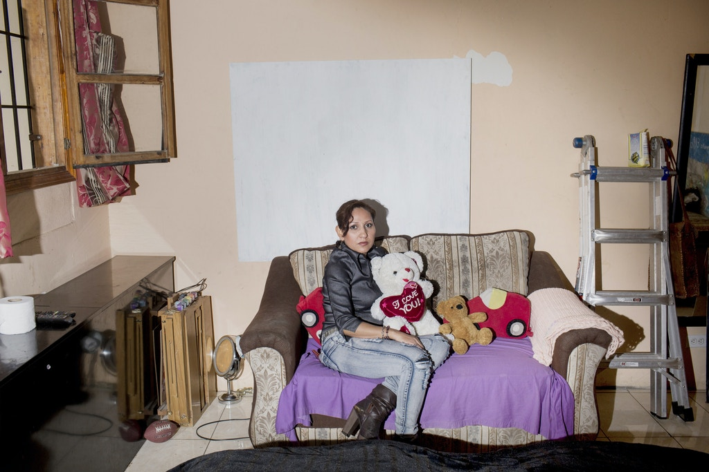 April 7, 2016. Tijuana, Mexico. Emma Sanchez Paulsen, a Dreamer Mom, poses for a portrait in her bedroom in her home  in Tijuana. Sanchez Paulson is married with three children to an American Veteran, but she was deported and barred from the US for ten years starting in 2006 because she had originally entered the US illegally. She still sees her husband and children as much as possible whenever they can come visit her from their home across the border in California, but desperately misses her family and is heart broken by missing the day to day parts of being a wife and mother.