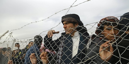 TOPSHOT - Iraqi refugees, who fled the Iraqi city of Mosul due to the fighting between government forces' and Islamic State (IS) group's jihadists, look from behind a fence at the UN-run al-Hol refugee camp in Syria's Hasakeh province, on December 5, 2016.Despite the war that is ravaging Syria and has displaced millions of its residents, the Iraqis are desperate to reach the UN-run Al-Hol refugee camp in Syria's Hasakeh province, where many are still trapped on the border between Iraq and Syria under jihadist fire. / AFP / DELIL SOULEIMAN (Photo credit should read DELIL SOULEIMAN/AFP/Getty Images)