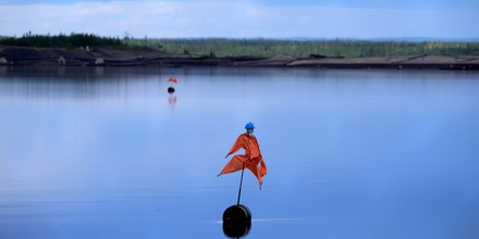 A scarecrow floats in a tailings pond outside Syncrude's mine site north of Fort McMurray, Alberta on June 3, 2016. Production at the plant continues after being briefly suspended during last month's raging forest fires threatened to burn through to the plant. / AFP / Cole Burston (Photo credit should read COLE BURSTON/AFP/Getty Images)