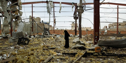 A Yemeni woman inspects the damage at a factory allegedly targeted by Saudi-led airstrikes in the Yemeni capital Sanaa on Sept. 15, 2016.