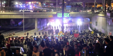Police (in background) form a line across the road as demonstrators shut down the 101 Freeway, a major thoroughfare in the city, following a rally to protest a day after President-elect Donald Trump's election victory in Los Angeles, California, late on November 9, 2016.Protesters burned a giant orange-haired head of Donald Trump in effigy, lit fires ins the streets and blocked traffic lanes late on November 9 as rage over the billionaire's election victory spilled onto the streets of US cities. From New York to Los Angeles, thousands of people in around 10 cities rallied against the president-elect a day after his stunning win, some carrying signs declaiming