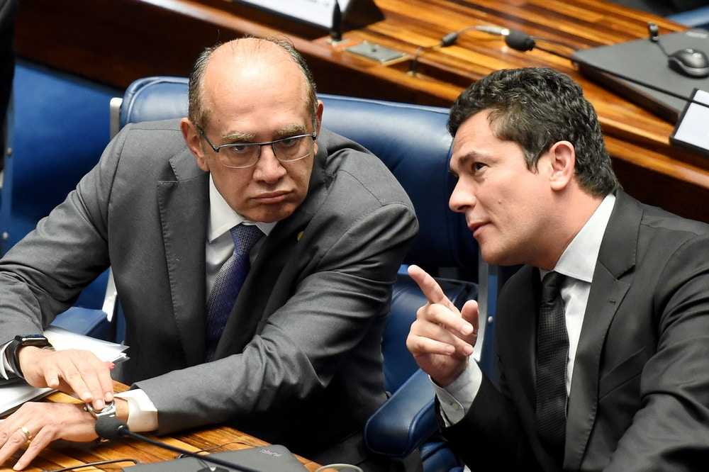 Supreme Court's Judge Gilmar Mendes (L) listens to Federal Judge Sergio Moro during a public hearing on the bill that establishes the abuse of authority for judges and prosecutors, in the Senate in Brasilia on December 1, 2016.<br /> Even with a strong reaction against the bill from the public, Calheiros tries to speed up approval in the Senate and Lower House. The controversial law is ostensibly meant to crack down on undeclared election campaign funds, a common practice in Brazilian politics that has been linked to large-scale corruption. Judges and prosecutors have branded this as a weapon to reduce the judiciary's independence. / AFP / EVARISTO SA        (Photo credit should read EVARISTO SA/AFP/Getty Images)