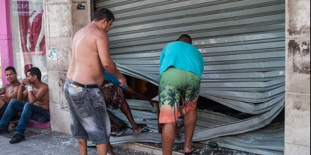 Men fix the broken shutter of their shop after burglars entered in Vila Velha, near Vitoria, eastern Brazil, on February 6, 2016. Brazil's government authorized deployment of troops Monday to the coastal city of Vitoria, which has been left at the mercy of criminals following a police strike. / AFP / Vinicius Moraes (Photo credit should read VINICIUS MORAES/AFP/Getty Images)