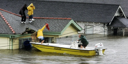 FILE - In this Aug. 29, 2005 file photo, Bryan Vernon and Dorothy Bell are rescued from their  rooftop after  Hurricane Katrina hit, causing flooding in their New Orleans neighborhood. The most destructive storm in U.S. history and also one of the deadliest, Katrina was a Category 3 storm with estimated maximum winds of 125 mph when it made landfall near Buras, La., on Aug. 29, 2005. Broken levees left most of New Orleans inundated. Damage was estimated at $75 billion, though rebuilding costs have far exceeded the initial damage. Katrina was blamed for around 1,200 deaths. (AP Photo/Eric Gay, File)