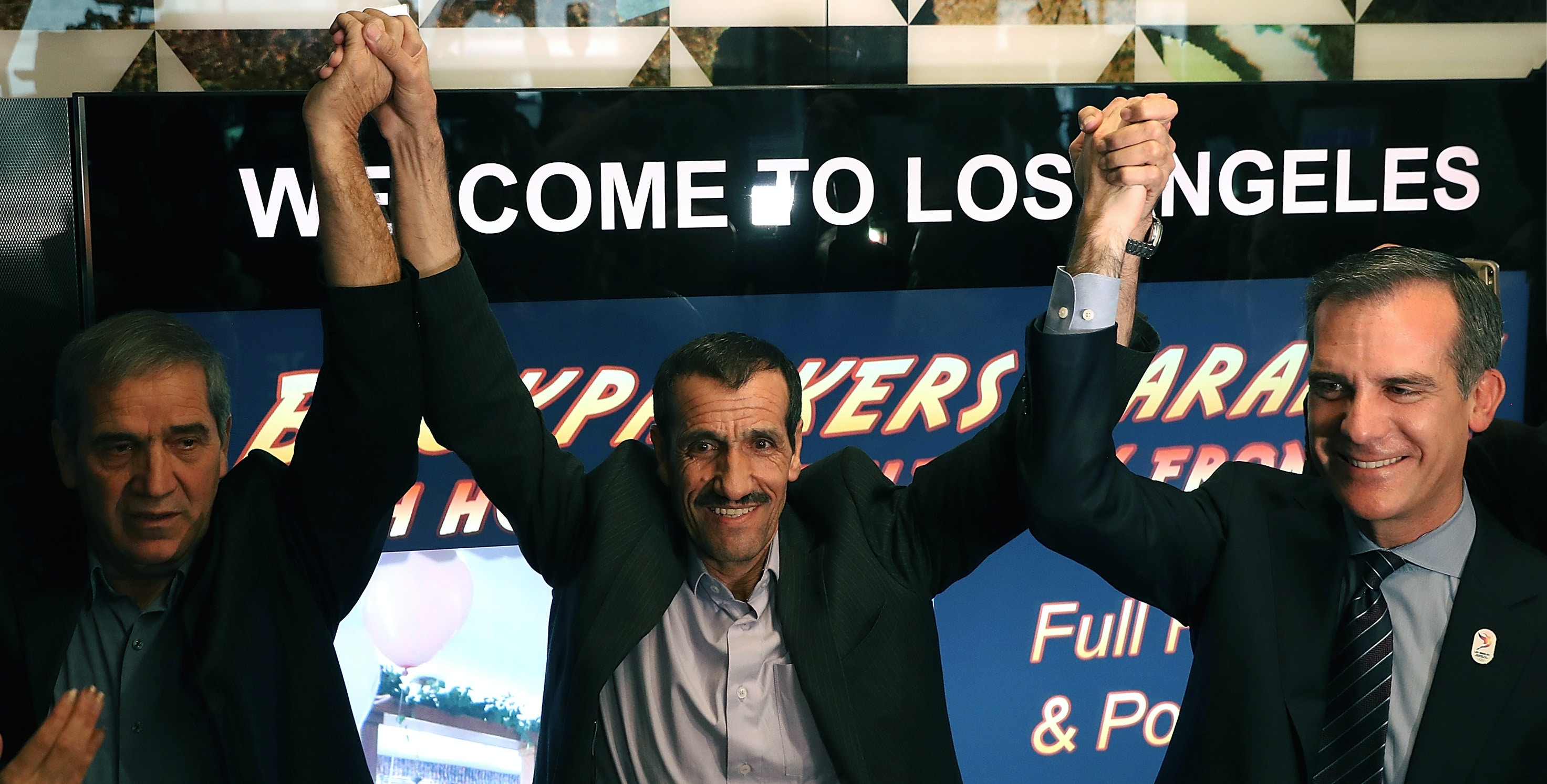 LOS ANGELES, CA - FEBRUARY 02:  (L-R) Hossein Vayeghan raises his arms with his brother, Iranian citizen Ali Vayeghan and  Los Angeles Mayor Eric Garcetti as he arrives at Los Angeles International Airport on February 2, 2017 in Los Angeles, California.  Iranian citizen Ali Vayeghan was detained and sent back to Iran after arriving in the United States on the day that U.S. President Donald Trump's travel ban was implemented.  (Photo by Justin Sullivan/Getty Images)