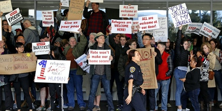 SAN FRANCISCO, CA - JANUARY 28: A police officer walks past demonstrators at the international arrival terminal at San Francisco International Airport during a rally against a ban on Muslim immigration on January 28, 2017 in San Francisco, California. President Donald Trump signed an executive order Friday that suspends entry of all refugees for 120 days, indefinitely suspends the entries of all Syrian refugees, as well as barring entries from seven predominantly Muslim countries from entering for 90 days. (Photo by Stephen Lam/Getty Images)