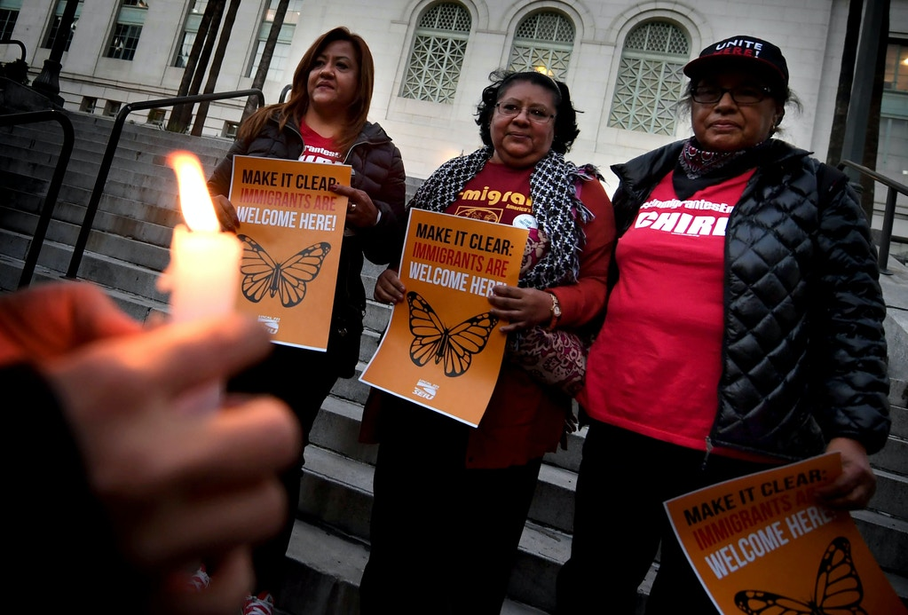 "Migrant rights groups look on during a vigil to protest against US President Donald Trump's new crackdown on ""sanctuary cities"", outside the City Hall in Los Angeles on January 25, 2017.Some 300 such cities, counties or states -- from New York to Los Angeles -- exist throughout the United States, and many of them have vowed since Trump's election to protect the estimated 11 million undocumented migrants living in the country. / AFP / Mark RALSTON (Photo credit should read MARK RALSTON/AFP/Getty Images)"