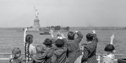 A group of young Austrian immigrants wave to the Statue of Liberty upon their arrival in America aboard the S.S. Harding. The fifty Jewish children, who were greeted by their new adoptive families, were fleeing Nazi persecution in their homeland.