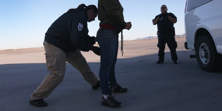 A security contractor frisks a female immigration detainee from Honduras ahead of a deportation flight to San Pedro Sula, Honduras on February 28, 2013 in Mesa, Arizona. U.S. Immigration and Customs Enforcement (ICE), operates 4-5 flights per week from Mesa to Central America, deporting hundreds of undocumented immigrants detained in western states of the U.S. With the possibility of federal budget sequestration, ICE released 303 immigration detainees in the last week from detention centers throughout Arizona. More than 2,000 immigration detainees remain in ICE custody in the state. Most detainees typically remain in custody for several weeks before they are deported to their home country, while others remain for longer periods while their immigration cases work through the courts. (Photo by John Moore/Getty Images)