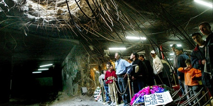 During a memorial service in Baghdad, Iraqis gather around a bomb hole in the ceiling of the Al-Amariya shelter Sunday Feb. 16, 2003, where more than 400 people were killed in a U.S.-led missile attack during the Gulf War. Iraqis opened a new memorial center outside the Al-Amariya shelter Sunday to mark the 12 year anniversary of the attack. (AP Photo/David Guttenfelder)