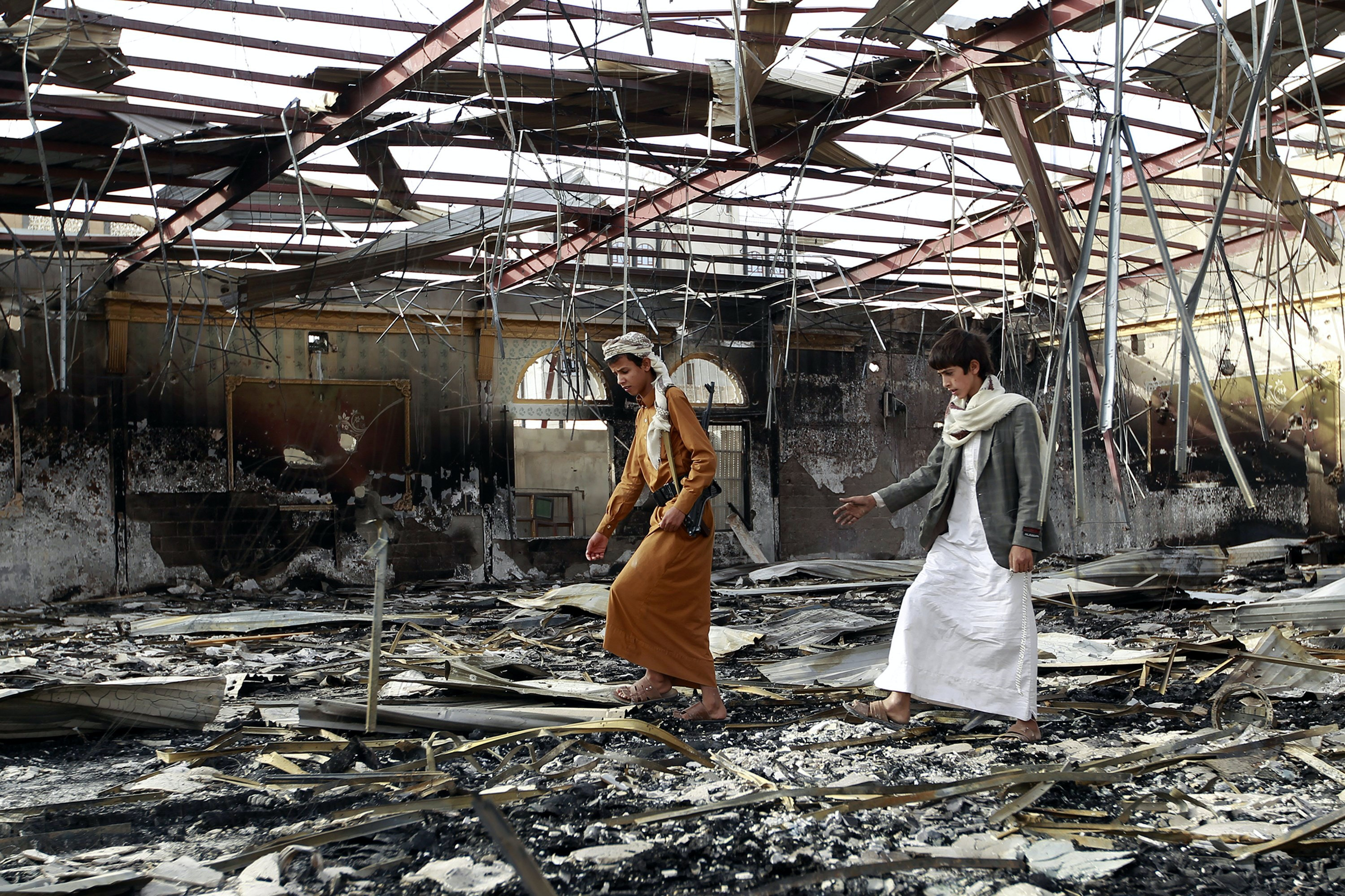 "Armed Yemenis walk on the debris at a wedding hall which was reportedly hit by a Saudi-led coalition air strike in the capital Sanaa, on July 10, 2015, a few hours before a humanitarian pause was to take effect. The humanitarian pause in the war in Yemen will be ""useless"" because rebels and their allies have shown no readiness to abide by it, a Saudi official said. AFP PHOTO / MOHAMMED HUWAIS        (Photo credit should read MOHAMMED HUWAIS/AFP/Getty Images)"