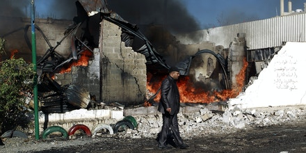 A Yemenis man walks past flames rising from the ruins of buildings destroyed in an air-strike by the Saudi-led coalition on February 10, 2016 in the capital Sanaa. / AFP / MOHAMMED HUWAIS        (Photo credit should read MOHAMMED HUWAIS/AFP/Getty Images)