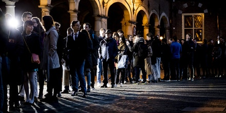 People queue to cast their votes for the general elections, on March 15, 2017. Millions of Dutch flocked to the polls today in a test of the