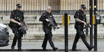 Armed police officers enter the Houses of Parliament in London, Wednesday, March 23, 2017 after the House of Commons sitting was suspended as witnesses reported sounds like gunfire outside. The leader of Britain's House of Commons says a man has been shot by police at Parliament. David Liddington also said there were