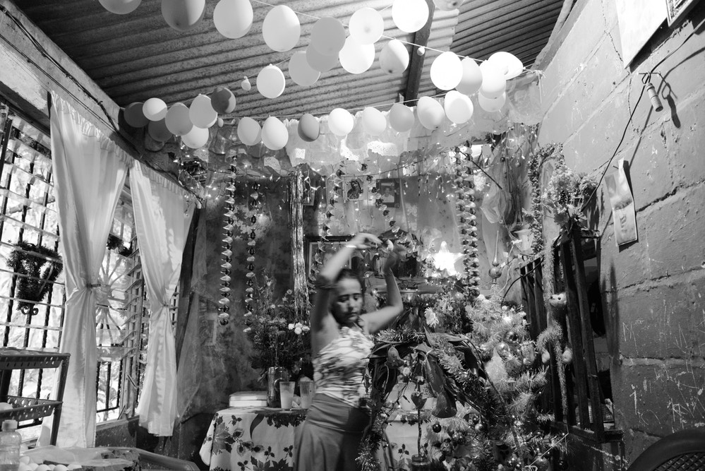 "A woman with Christmas decorations in the small storefront inside her home where she sells food to migrants near the freight train tracks for ""La Bestia,"" a freight train many migrants used to ride north.The U.S.-funded Plan Frontera Sur has increased enforcement on the train, so migrants have turned instead to walking and taking buses. This is a particularly dangerous area for them, with many robberies and attacks."