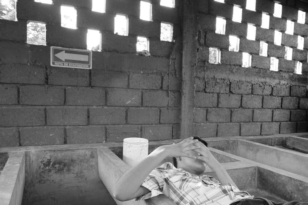 A 13-year-old Honduran boy reclines in a sink for washing clothes at a refuge for families seeking asylum in Tapachula, Chiapas. Gang members killed his father, a police officer, six years ago. They demanded his mother hand over half of the money she earned selling food on the street, then later insisted the boy join the gang or his 15-year-old sister become their girlfriend, so the family fled.They now live in a shelter for asylum-seekers as their application for refugee status is processed. They're grateful for the refuge, but the donated food is often scarce and they are allowed to leave just once a day and must be back by 6:00PM. They are terrified that gang members will spot them, as the city is full of migrants from Honduras.