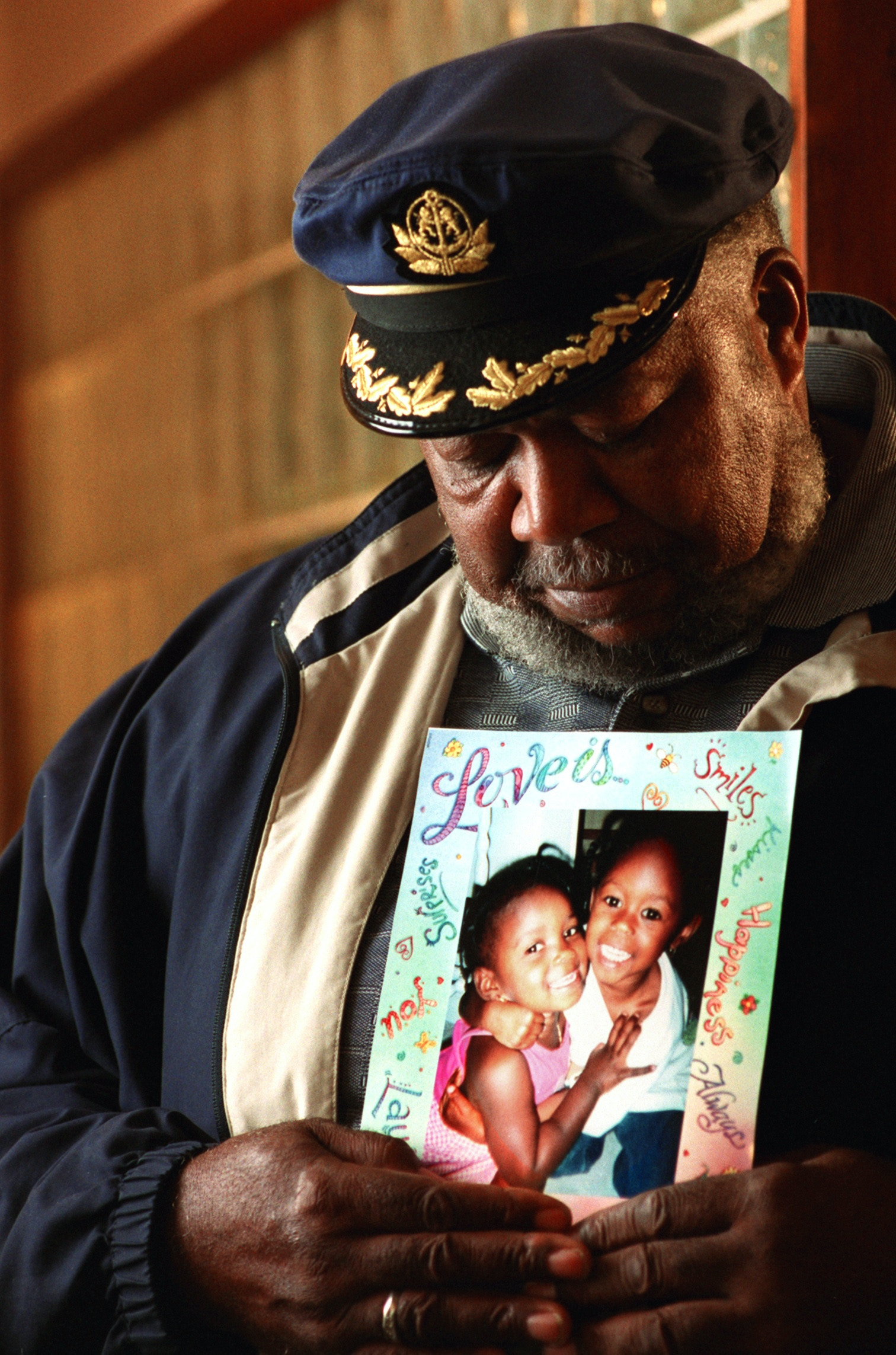 Ibrahim B. Ahmed holds a photo of two of his granddaughters who died in a house fire last November. His daughter, Angela Garcia, was charged with aggravated murder for their deaths. June 6, 2000 (The name is spelled differently in the story : Ibrahim Ahmad) (Lonnie Timmons III/Plain Dealer)