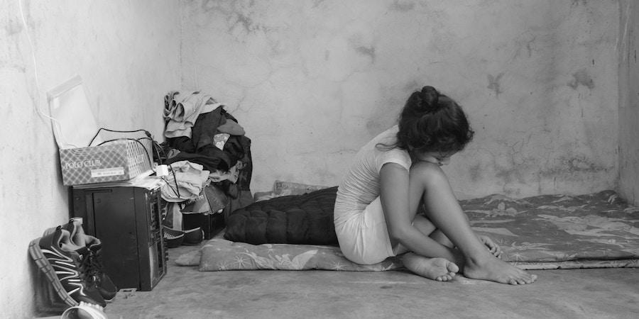 Migrante de 10 anos, que fugiu de ameaças de gangues de El Salvador, senta-se sobre os lençóis que sua família usa como cama em uma casa alugada em Tapachula, Chiapas.