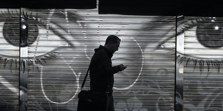 FILE - In this Thursday, Oct. 31, 2013, file photo, a man looks at his cellphone as he walks on the street in downtown Madrid. The National Security Agency has implanted software in nearly 100,000 computers around the world — but not in the United States — that allows the U.S. to conduct surveillance on those machines, The New York Times reported Tuesday, Jan. 14, 2014. (AP Photo/Francisco Seco, File)