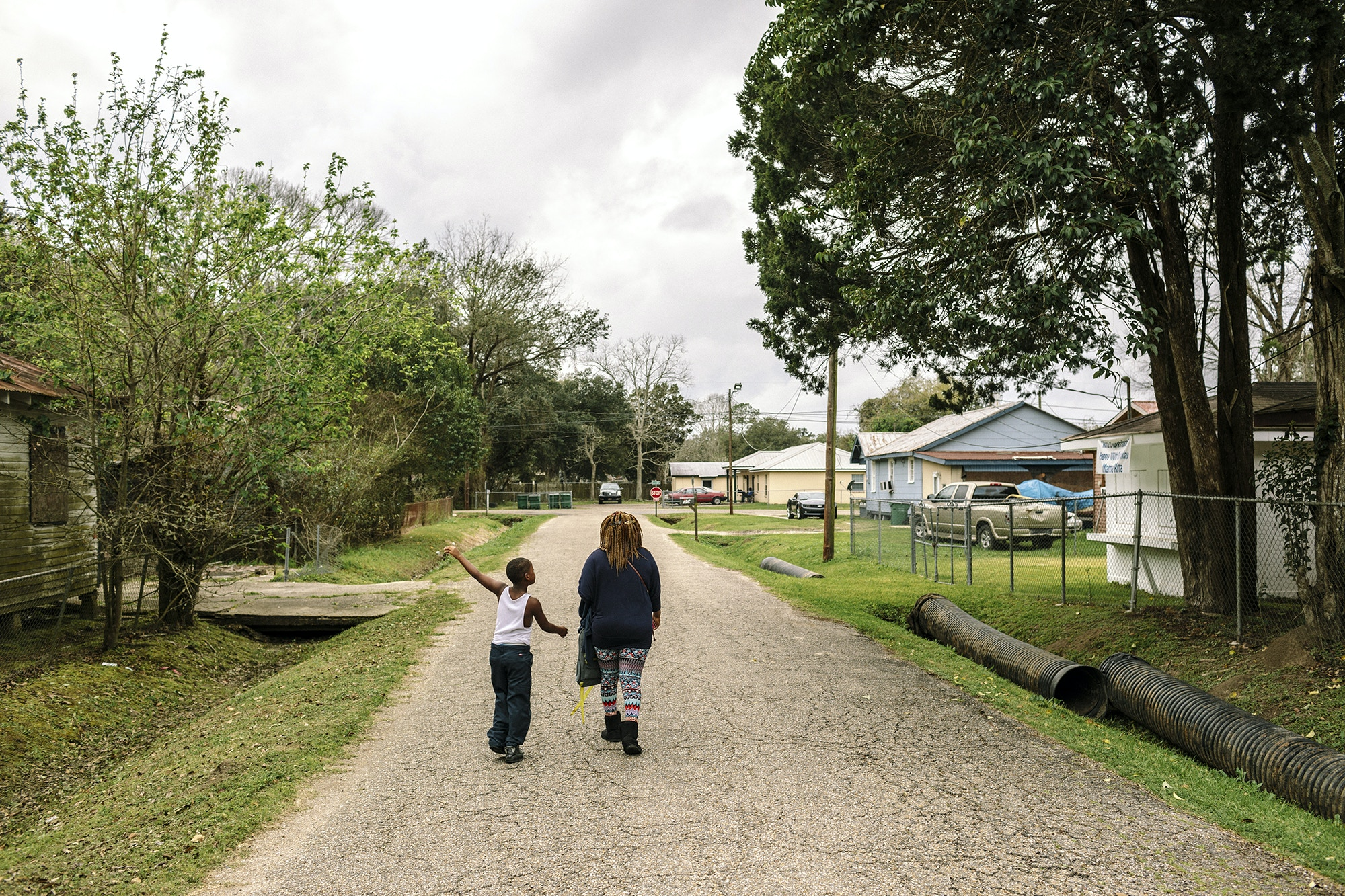 Reserve, LA - Feb 20, 2017 - A young boy walks home from school along Robinet Drive, one block from the fenceline of the Dupont/Denka plant.