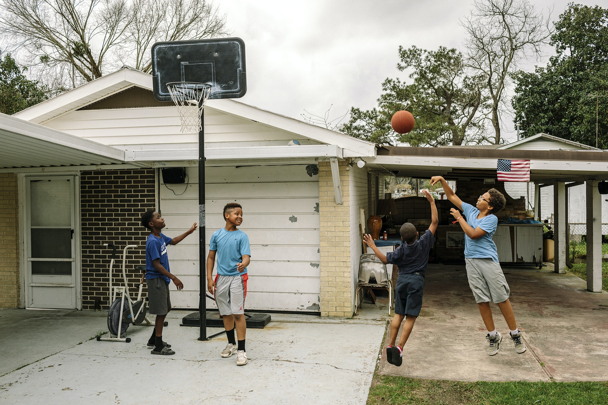 Reserve, LA - Feb 20, 2017 - Local youth play basketball after school in the driveway of a home located one block from the fenceline of the Dupont/Denka plant.