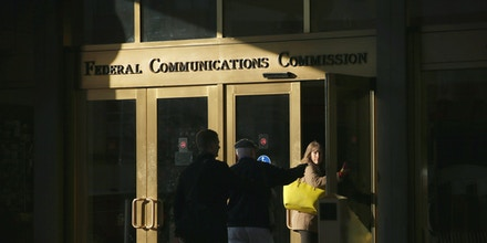 People enter the Federal Communications Commission building in Washington, DC, on December 11, 2014 .