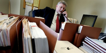 Attorney Curt Winegarner talks on the phone while surrounded by his pending case files at the Missouri State Public Defender System office in Kansas City, Missouri. (David Pulliam/Kansas City Star/MCT via Getty Images)