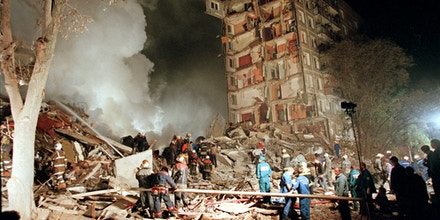 Fire and smoke rises from a destroyed apartment building as Russian Emergency Situations Ministry officers and firefighters try to save people in Moscow, in this  Thursday, Sept. 9, 1999 photo as a massive explosion shattered a nine-storey apartment building.  Hoping to shame the government into ordering an investigation, a small liberal party on Tuesday showed the Russian premiere of a film alleging the secret service organized four 1999 bombings that helped spark Moscow's second Chechen war and catapault Vladimir Putin to the presidency. (AP Photo/Ivan Sekretarev)