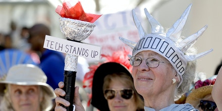 Katherine Forrest, with the group Raging Grannies, holds up a torch during a Tech Stands Up rally on Pi Day, Tuesday, March 14, 2017, outside City Hall in Palo Alto, Calif. Subcontracted tech service workers and direct tech employees rallied together to call on their companies and CEOs to stand with their workers against injustice and hate. (AP Photo/Eric Risberg)