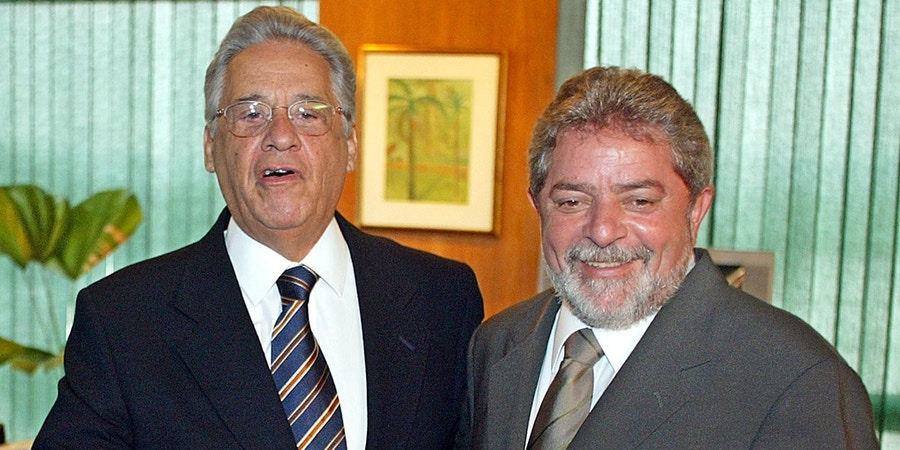 Brazilian newly elected president Luiz Inacio Lula da Silva (R) smiles as ruling president Fernando Henrique Cardoso jokes with the photographers, 29 October 2002, during a meeting at the presidential Palace in Brazilia, Brazil. Lula da Silva was elected with some 53 millions vote last 27 October, and will starts his governement period on January 2003.    AFP  PHOTO  Antonio SCORZA (Photo credit should read ANTONIO SCORZA/AFP/Getty Images)